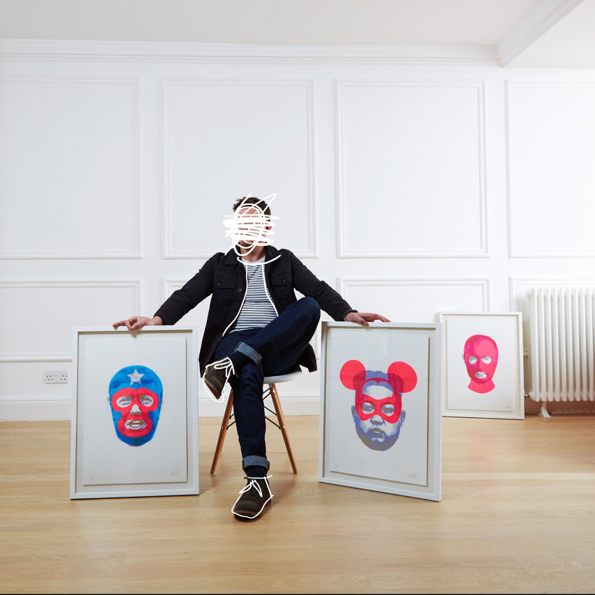 Heath Kane sitting holding two of his prints